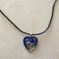 Heart Shaped Silver Pendant with Charms and a Black cord.