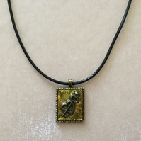 Small Bronze Pendant With a Bronze Charm on a Black Cord.