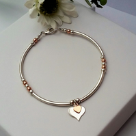 Heart bracelet in sterling silver and rose gold.