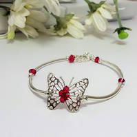 Filigree butterfly bracelet adorned with red Swarovski crystals