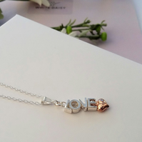 Sterling Silver pendant spelling love with a rose gold heart