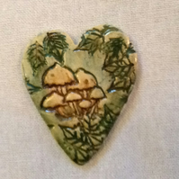 Heart shaped ceramic  brooch decorated with toadstalls