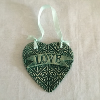 Ceramic Heart Wall Hanger LOVE on Patterned Background.