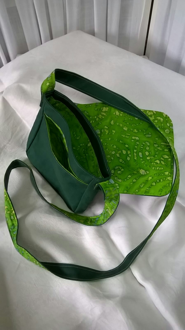 Small dark green canvas cross-body bag with lime green lining and pockets