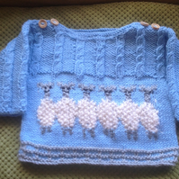 Hand knitted long sleeved jumper with a line of sheep, with embroidered details