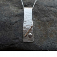 Sterling Silver Textured Pendant With 9ct Gold decoration.