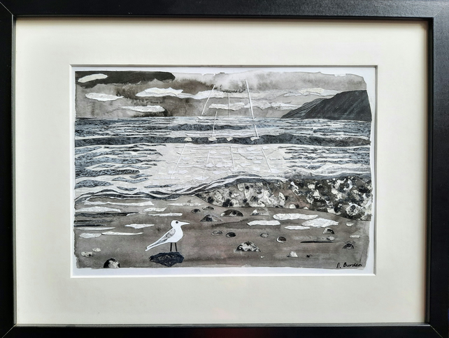 """Breaking through the clouds"". Framed coastal collage in black and white."
