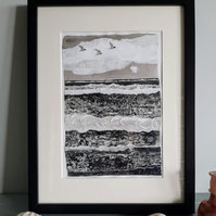 Three birds flying.  Framed black and white collaged seascape.