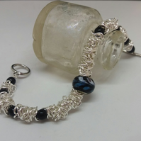 BR186  Scrunched chain link bracelet with black beads.