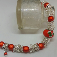 Scrunched chain bracelet with orange miracle beads.