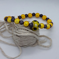 BR370 Yellow and deep plum miracle bead bracelet with glass feature bead