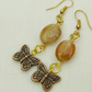 Brown Oval Agate Bead Earrings With A Bronze Butterfly Charm,