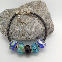 Blue and Black European Lampwork Bead Bracelet on a Black Plaited Leather Band