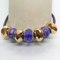 Blue and Gold European Lampwork Bead Bracelet on a Black Plaited Leather Band
