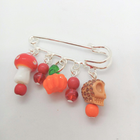 Kilt Pin with Toadstool Skull & Pumpkin Charms and a Red & Orange Beaded Charms