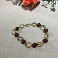 Gold plated Aluminium anodised bracelet with red frosted beads