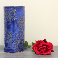 Floating blue vase adorned with hand carved nature inspired pattern