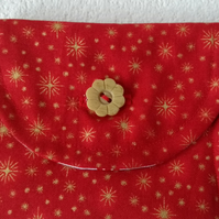 Button fastening coin or card purse with gold stars on a red background