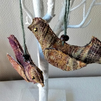 A pair of hanging decorative love birds in brown and purple tweed fabric.