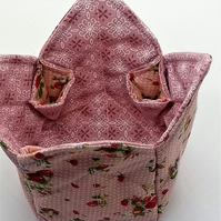 A quilted fabric pot with strawberry print on pink background fabric