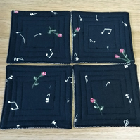 A set of 4 quilted coasters with music note and rose print.