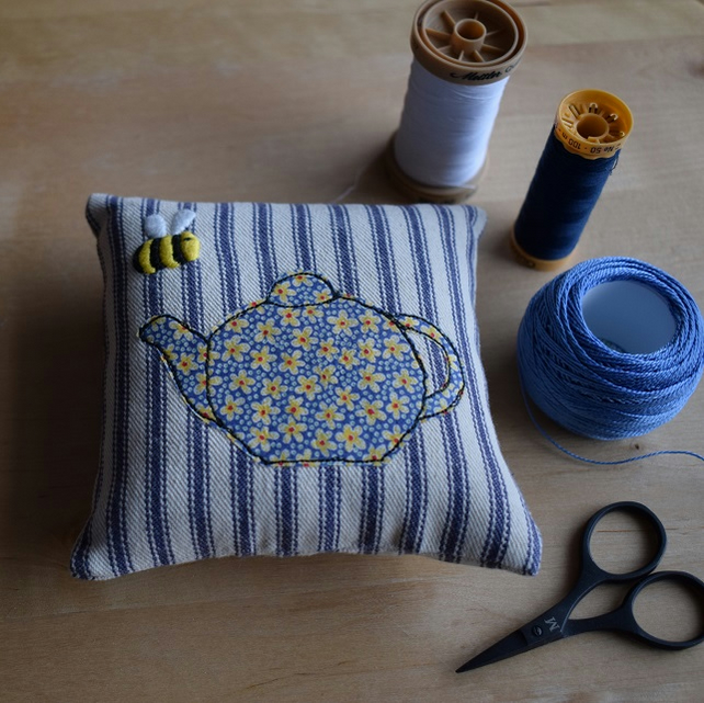Blue ticking pincushion with an embroidered bee and Liberty teapot.