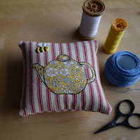 Red ticking pincushion with an embroidered bee and Liberty teapot.