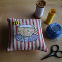 Red ticking pincushion with an embroidered bee and Liberty teacup and saucer.