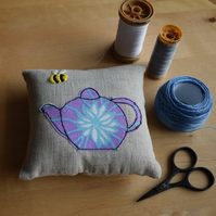 Linen pincushion with an embroidered bee and vintage teapot.