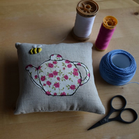 Linen pincushion with an embroidered bee and Liberty teapot.