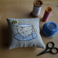 Linen pincushion with an embroidered bee and a Liberty teacup and saucer.