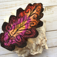 Embroidered oak leaf brooch.
