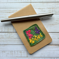 Pocket embroidered flower notepad.