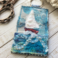 Up cycled seascape keyring with sail boat.