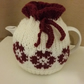 Cream tea cosy with dark red flowers