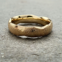 Yellow gold designer wedding ring, melted and forged textured band