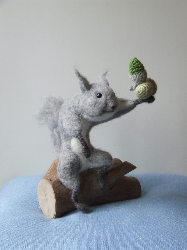 Needle-felt squirrel perched on log