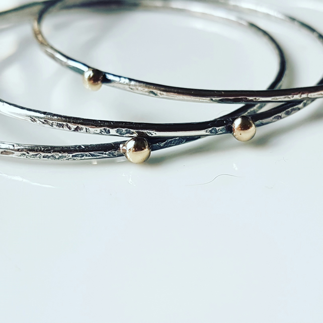 Stacking bangles with an organic texture and a 9ct gold ball