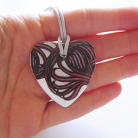 Filigree Artwork Design on Heart Shaped Ceramic Pendant on Grey Cord