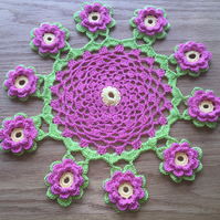 Table decoration crochet mat with intricate layered flowerin green & pink
