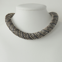 Beige and grey embroidered necklace.