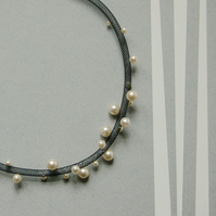 Contemporary faux pearl and black mesh necklace.