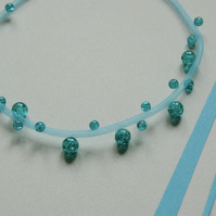 Blue mesh necklace with turquoise beads.