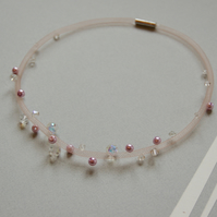 Pale pink mesh necklace with pink and crystal beads.