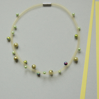 Yellow mesh necklace with green beads.