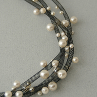 Black mesh necklace with cream faux pearls.