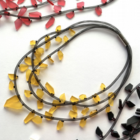Three strand yellow perspex bead necklace.