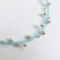 Pale blue necklace with cream faux pearls.