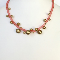 Red necklace with gold beads.