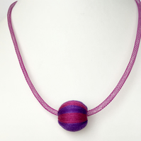 Purple and pink wrapped bead necklace on purple mesh tube.